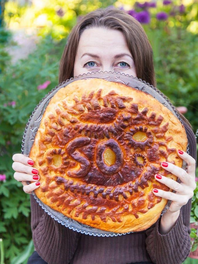 La donna tiene una torta di compleanno fotografia stock libera da diritti