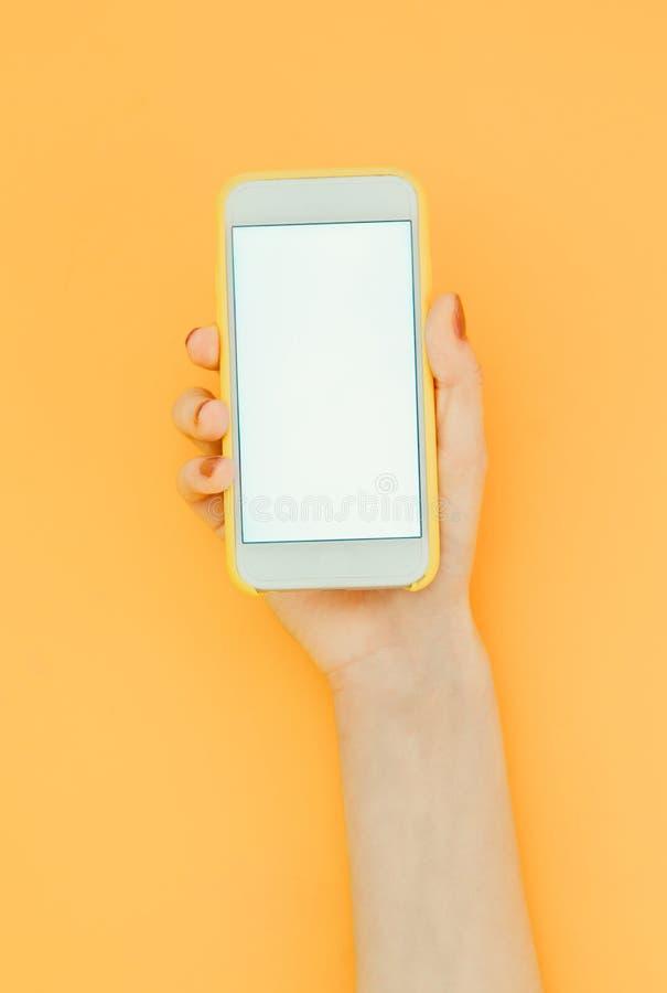 La donna tiene uno smartphone con uno schermo bianco sui precedenti arancio, posto per testo sullo schermo dello smartphone immagini stock