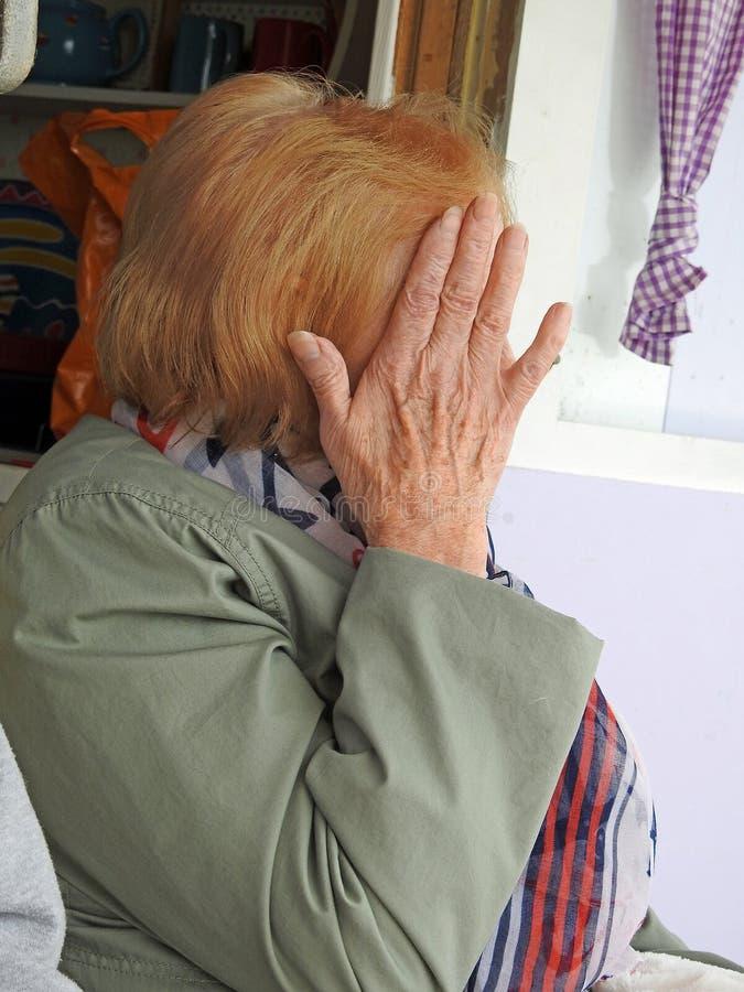 La donna timida della macchina fotografica nasconde il fronte dalla foto fotografie stock