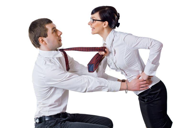 La donna tira l'uomo per un legame fotografie stock