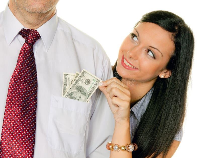 La donna tira un uomo dai soldi Tasche.Dollar immagini stock