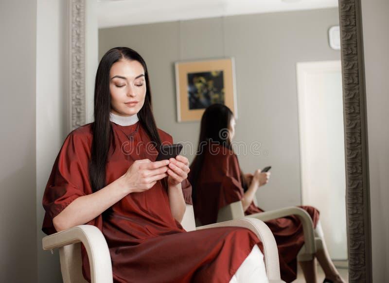 La donna tranquilla sta utilizzando il telefono cellulare nello studio di bellezza fotografia stock libera da diritti