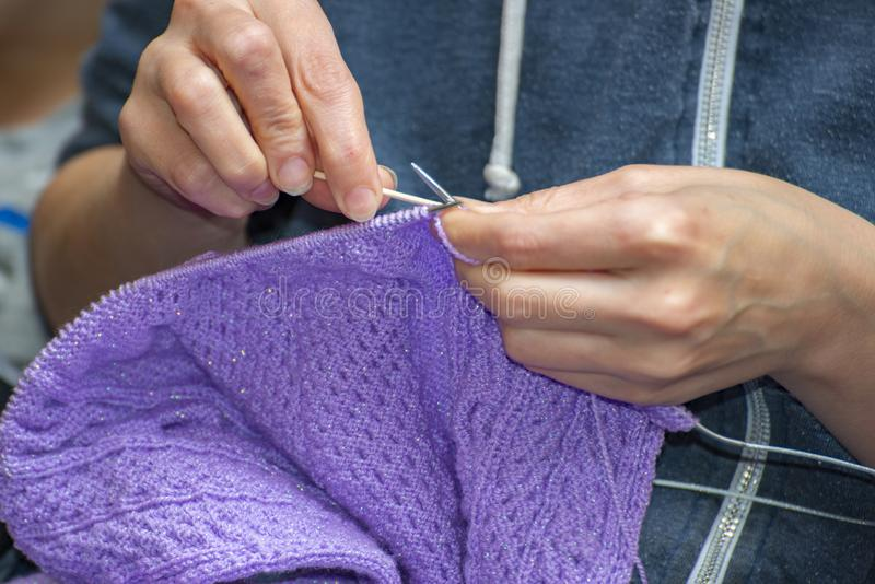 La donna tricotta i vestiti dai fili con i ferri da maglia fotografie stock
