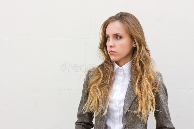 La donna triste si leva in piedi vicino alla parete bianca fotografia stock libera da diritti