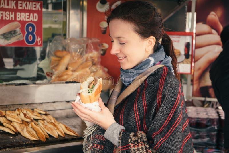 La donna turistica gode dell'alimento turco tradizionale della via a Costantinopoli fotografia stock libera da diritti