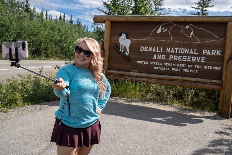 La donna turistica utilizza un bastone del selfie per prendere la foto davanti al segno del parco nazionale di Denali immagine stock