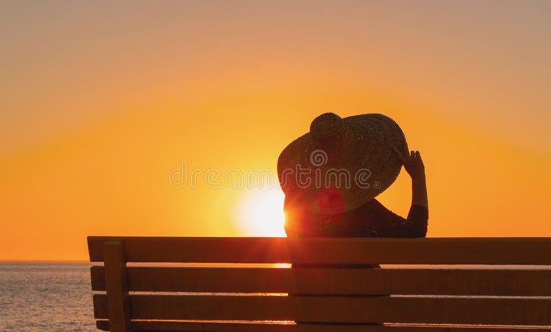 La donna in un grande cappello si siede su un banco e sugli sguardi al tramonto immagine stock libera da diritti