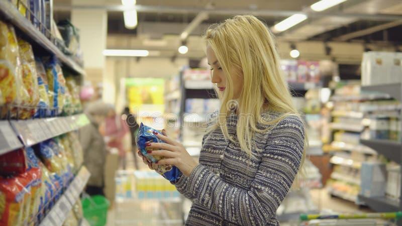 La donna in un supermercato che sta davanti al congelatore e sceglie il prodotto d'acquisto della pasta immagini stock