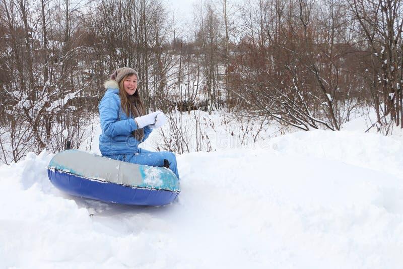 La donna in un vestito blu ha rotolato giù dalla montagna sulla tubatura della neve immagini stock
