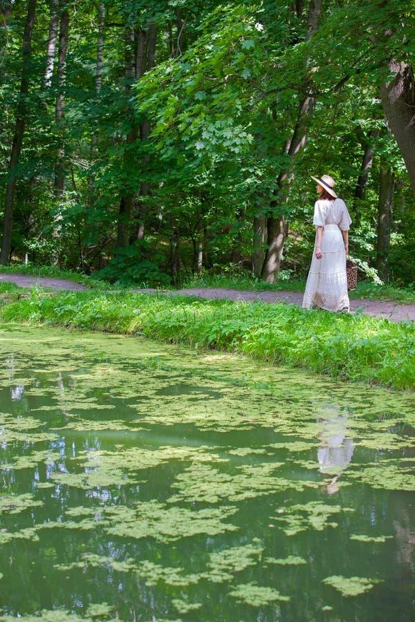 La donna in un vestito ed in un cappello bianchi va lungo la riva di uno stagno fotografie stock libere da diritti