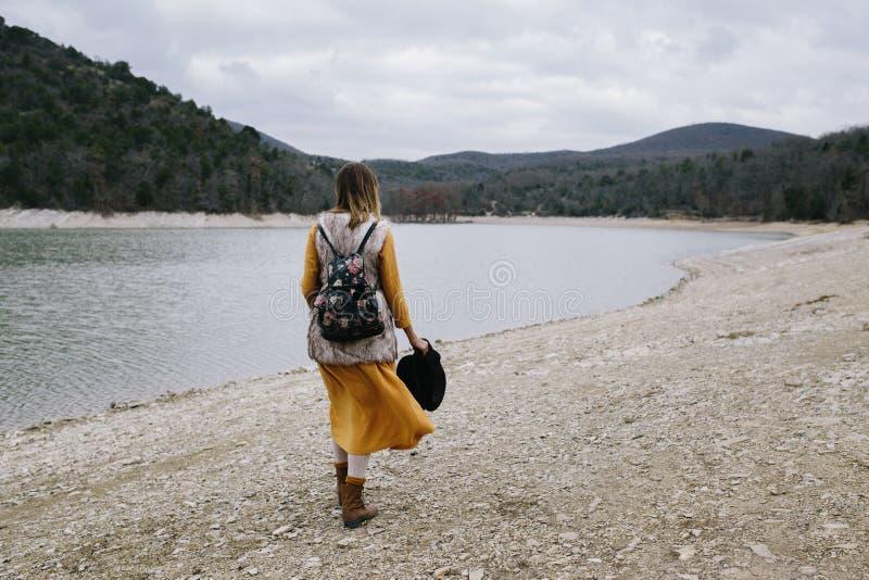 La donna in un vestito giallo e con lo zaino floreale cammina lungo la riva del lago immagini stock libere da diritti