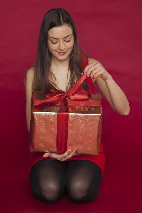 La donna in un vestito rosso apre un regalo fotografia stock