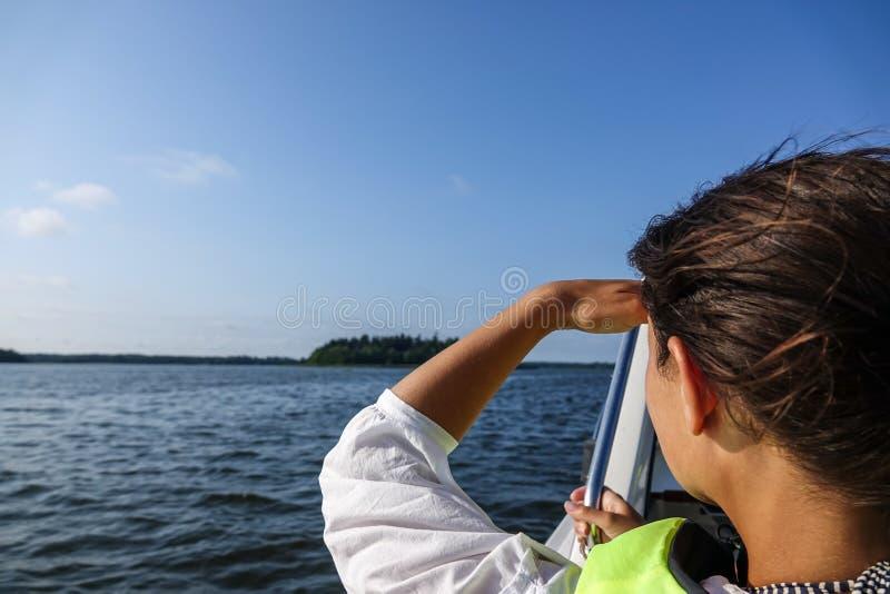 La donna in una barca che guarda fuori sopra l'oceano e la protegge occhi fotografia stock libera da diritti