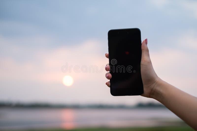 La donna la usa telefono cellulare all'aperto, si chiude su immagini stock