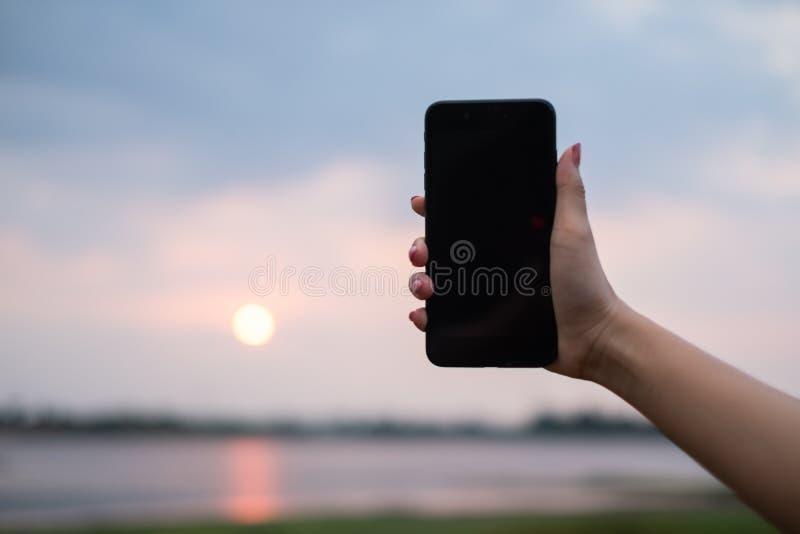 La donna la usa telefono cellulare all'aperto, si chiude su immagine stock