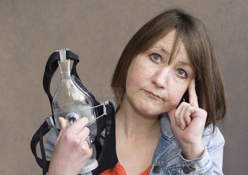 La donna utilizza il dispositivo per aiutare con COPD fotografia stock libera da diritti