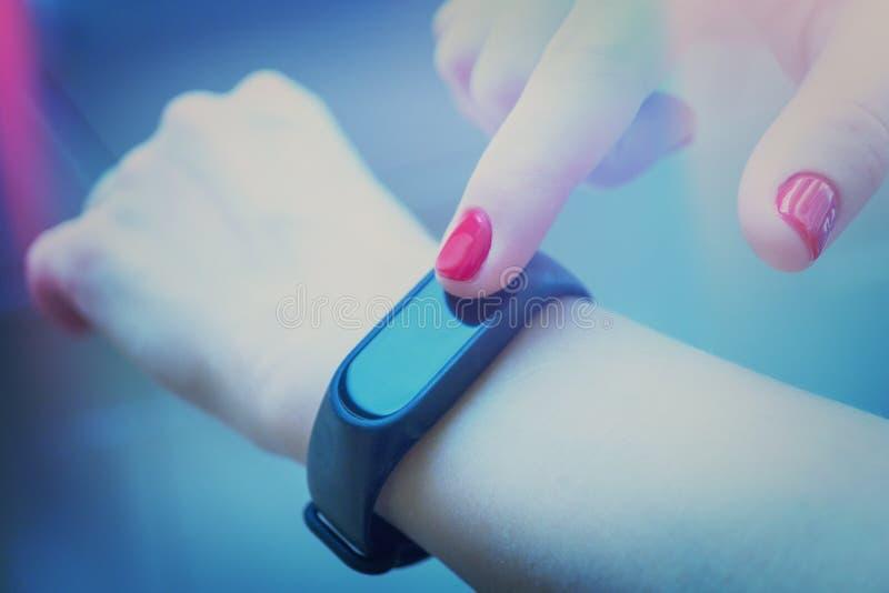 la donna utilizza un braccialetto di forma fisica Tonalità artistica Fuoco selettivo immagine stock