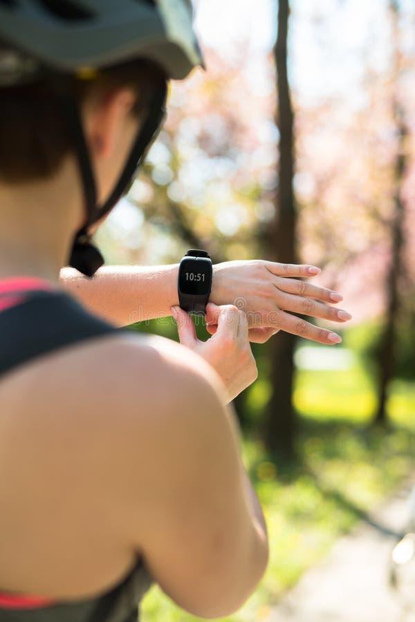 La donna utilizza un orologio astuto toccando il bottone ed il touch screen immagini stock libere da diritti
