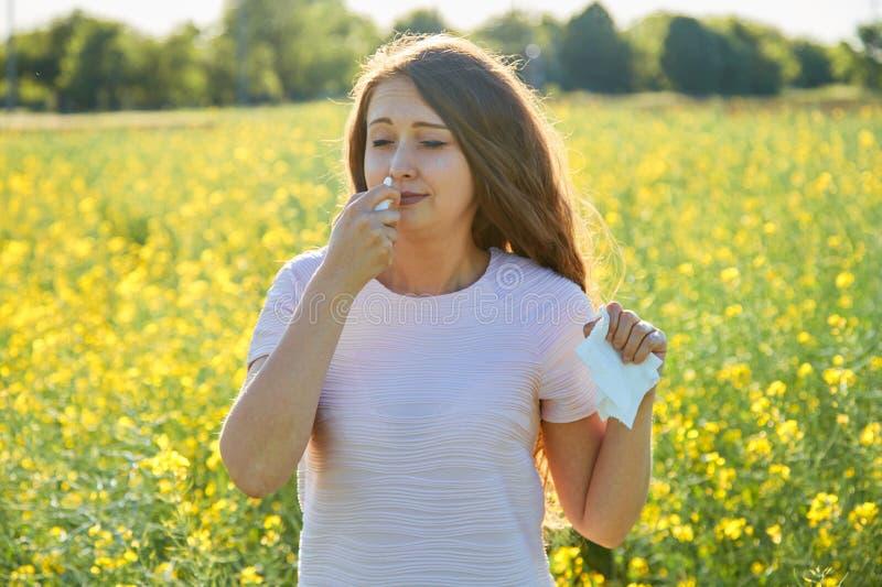 La donna utilizza uno spray nasale, contro le allergie della pianta, in un campo dei fiori fotografia stock