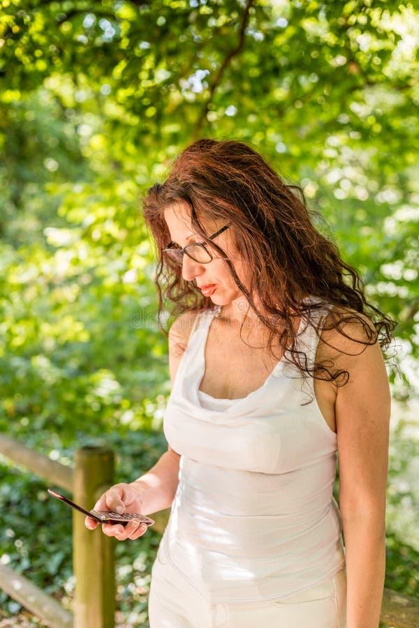 La donna vede il suo telefono cellulare immagine stock libera da diritti