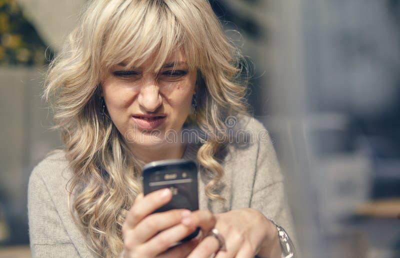 La donna vede qualche cosa di sgradevole sul telefono immagini stock libere da diritti