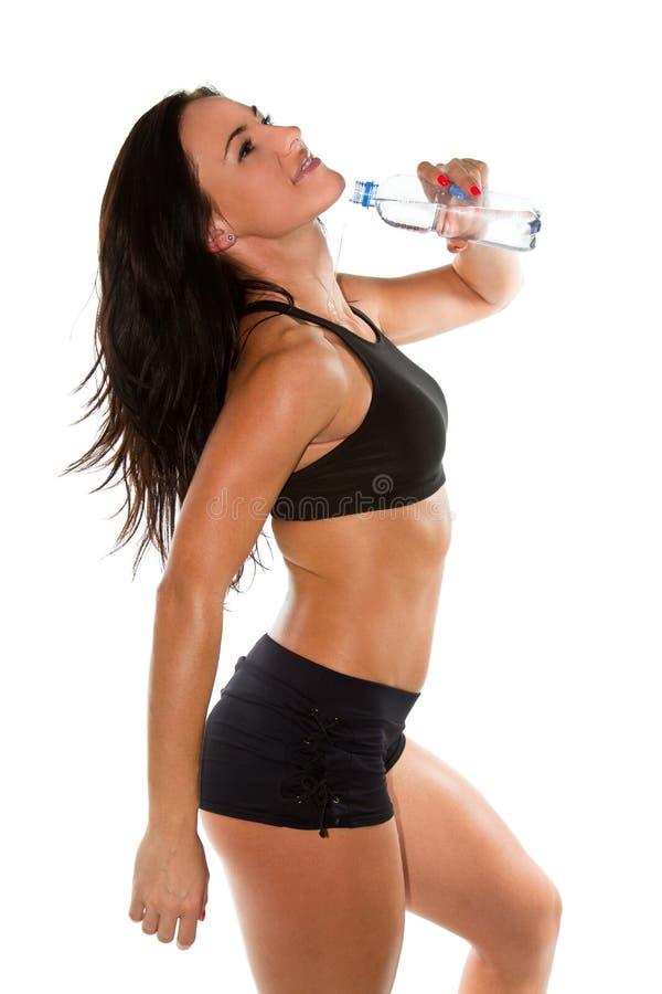 La donna versa l'acqua dalla bottiglia sul corpo immagine stock libera da diritti