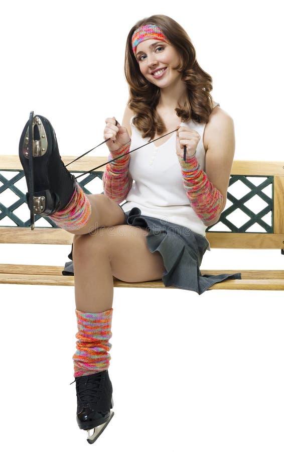 La donna veste in su i pattini di ghiaccio che si siedono sul banco immagine stock libera da diritti