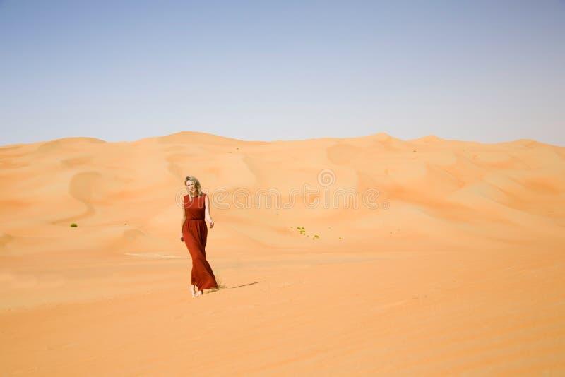 La donna vestita lunga cammina in deserto immagini stock