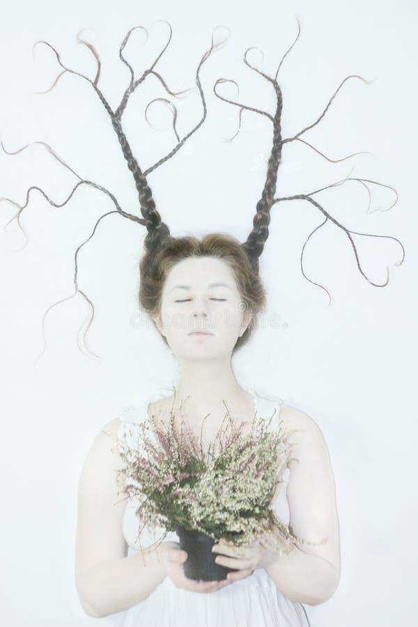 La donna in vestiti bianchi su un fondo bianco descrive l'inverno e la primavera, tenendo i fiori e un ramoscello con le foglie fotografia stock