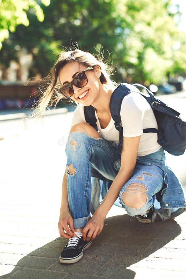 La donna in vestiti d'avanguardia fissa le scarpe da tennis sulla via fotografie stock