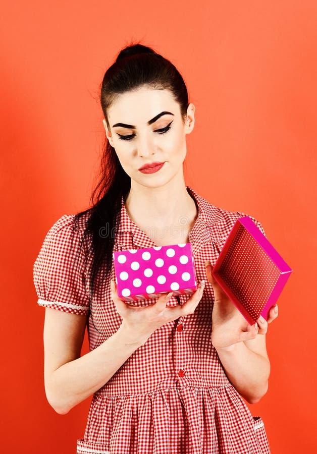 La donna in vestito alla moda apre il presente La ragazza con il fronte insoddisfatto, compone e pacchetto rosa Signora con il re fotografia stock