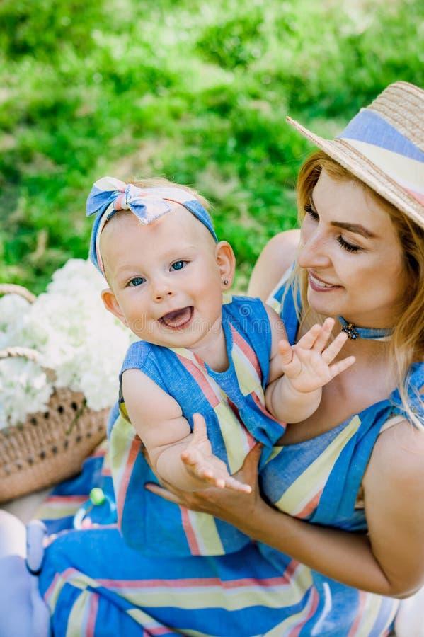 La donna in vestito blu alza sulla sua piccola figlia negli stessi vestiti immagine stock libera da diritti
