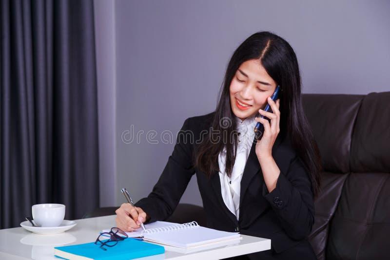 La donna in vestito che parla su un telefono cellulare e scrive un nessun immagini stock