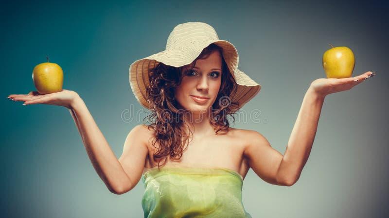 La donna in vestito ed il cappello tengono la mela gialla immagine stock