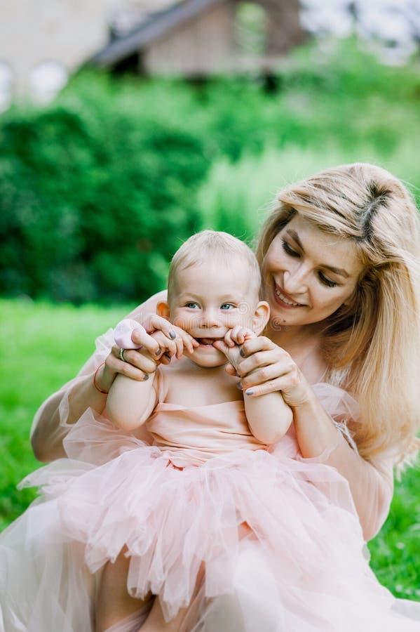 La donna in vestito rosa alza sulla sua piccola figlia negli stessi vestiti in parco immagini stock