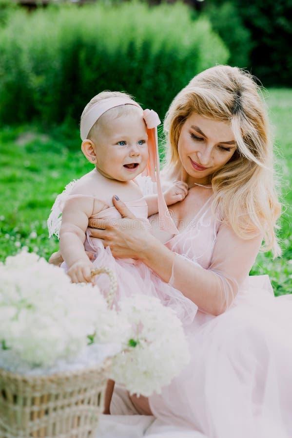 La donna in vestito rosa alza sulla sua piccola figlia negli stessi vestiti in parco fotografia stock
