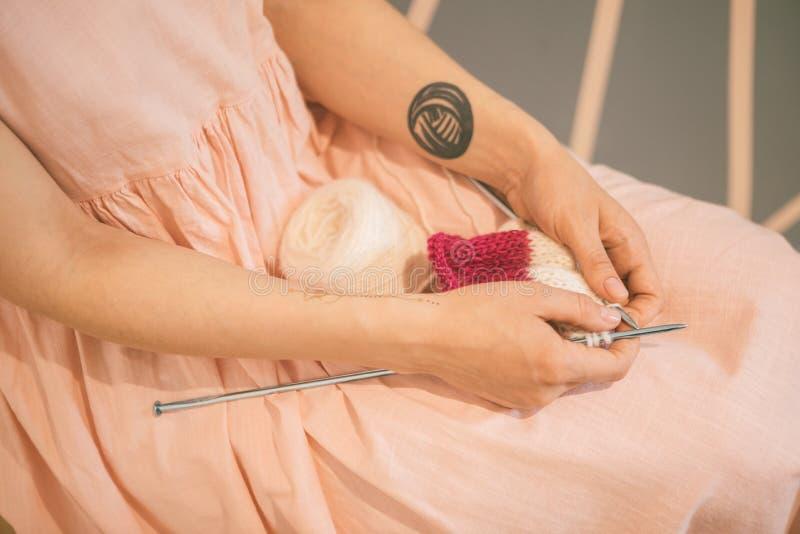 La donna in vestito rosa ha messo i ferri da maglia sulle sue ginocchia Umore accogliente caldo di colori immagine stock