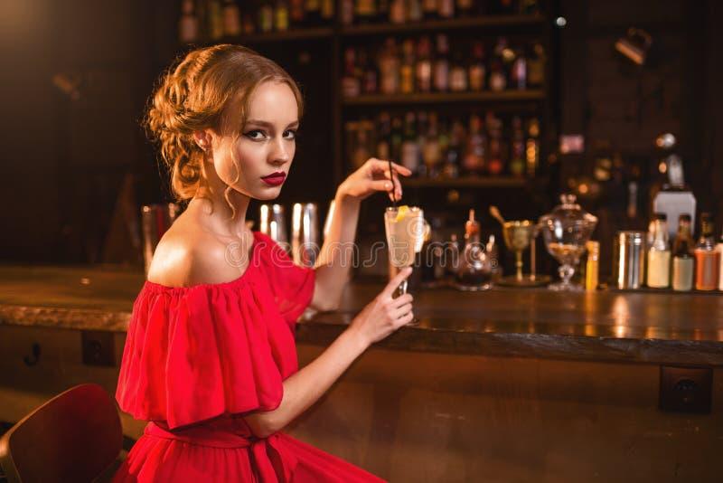 La donna in vestito rosso beve il cocktail al contatore della barra immagine stock