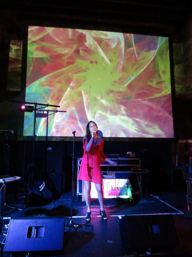 La donna in vestito rosso canta nel mic con il video overhea trippy di manifestazione immagini stock