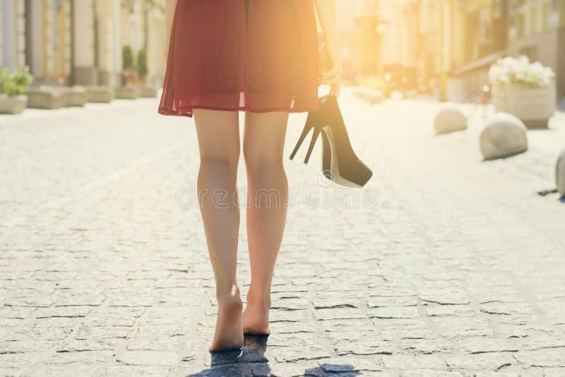 La donna in vestito, tacco alto calza la mano, camminante a piedi nudi nella città fotografie stock libere da diritti