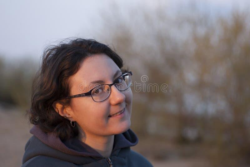 La donna in vetri sta sorridendo alla macchina fotografica immagini stock libere da diritti