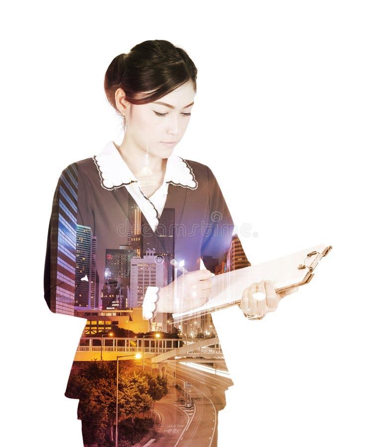 La doppia esposizione della donna di affari scrive sulla lavagna per appunti contro immagine stock