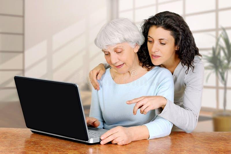 La dottrina della giovane donna insegna alla figlia di un computer portatile anziano della donna immagini stock