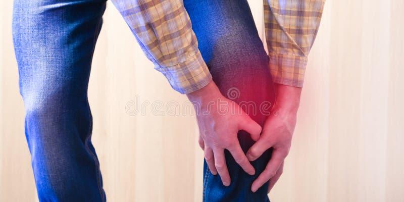 La douleur du fond rouge L'homme a saisi son genou dans un ajustement de douleur r photos libres de droits