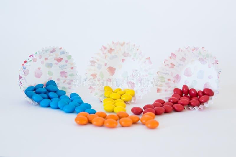 La dragée ronde bleue, jaune et rouge de sucreries a versé hors des paniers de papier photo stock