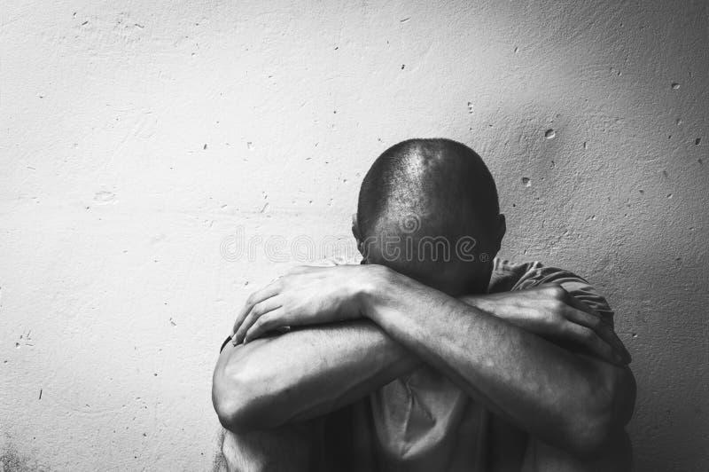La droga y el alcohol sin hogar del hombre envician sentarse solo y deprimido en la calle que siente concentrados documental ansi fotos de archivo
