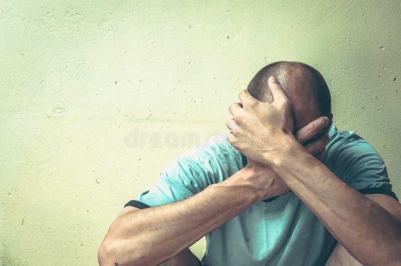 La droga y el alcohol sin hogar del hombre envician sentarse solo y deprimido en la calle en la sombra que siente ansiosa y sola, imagenes de archivo