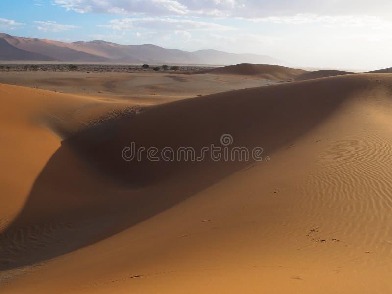 La duna di sabbia di forma astratta e la pentola rosse arrugginite naturali del sale di vasto deserto abbelliscono il fondo con l immagini stock libere da diritti