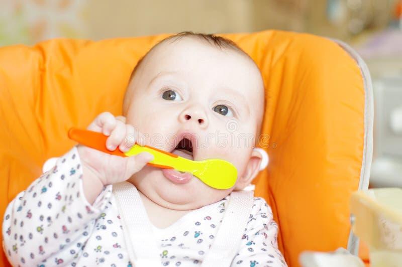 La edad del bebé de 5 meses con una cuchara se sienta en una silla de los bebés foto de archivo