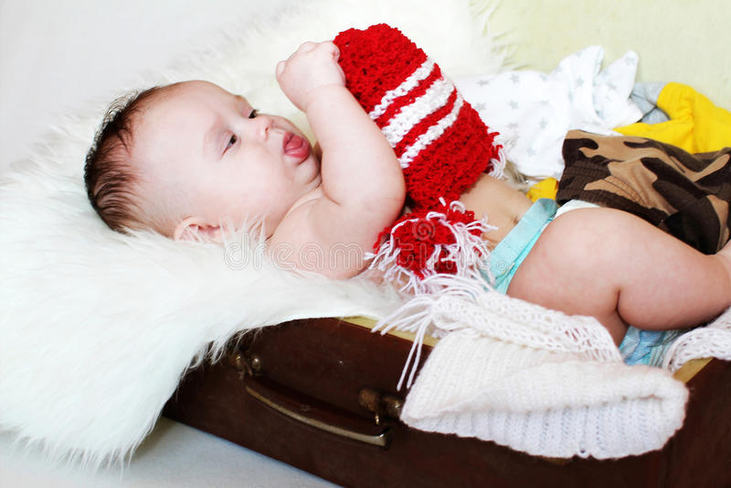 La edad del bebé de 3 meses mira el sombrero rojo, mintiendo en una maleta imagen de archivo libre de regalías